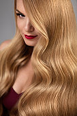 Hair Style. Beautiful Woman With Healthy Wavy Long Blonde Hair