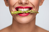 Healthy Diet. Beautiful Woman Mouth Holding Fresh Asparagus