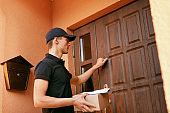 Delivery Service. Courier With Package Near Clients Door