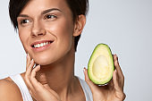 Skin Care And Beauty. Beautiful Woman Holding Avocado Near Face