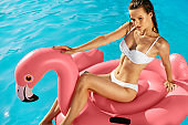 Summer Style. Woman On Pink Flamingo In Swimming Pool Water.