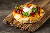 Pie in the oriental style. Filo pastry with tomato and mozzarella. Dark background. Vegetarian food.