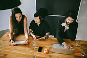 Overhead image of a young design team working in a small startup office in Berlin