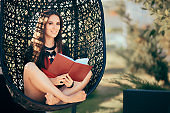 Summer Girl Reading a Novel Outdoors in Nest Chair