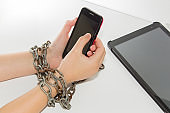 Iron chain ties together hands and smartphone - mobile phone addiction concept.