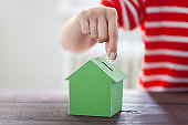 Woman putting coin In house piggy bank