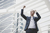 Successfully of young businessman keeping arms raised and expressing positivity while standing outdoors 'n