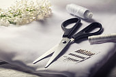 Background with sewing tools. Scissors, bobbins with thread and needles and textile on white table.
