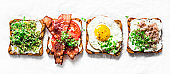 Variety of sandwiches for breakfast, snack, appetizers - avocado puree, fried egg, tomatoes, bacon, cream cheese, smoked mackerel grilled whole grain bread sandwiches. On a light background, banner view