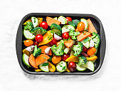 Raw fresh vegetables on a baking sheet. Sweet potato, zucchini, sweet pepper, cherry tomatoes, garlic, broccoli cabbage-ingredients for healthy vegetarian lunch on white background, top view