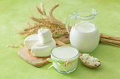 Shavuot concept - dairy products and wheat on green wood background
