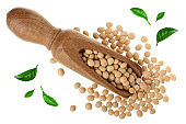 soybeans in wooden scoop decorated with green leaves isolated on white background top view