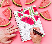 drawing a bright watermelon sketch with markers on pink background