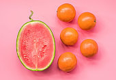 creative layout of fruit. a watermelon and oranges on pink background