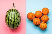 creative layout of fruit. a watermelon and oranges on blue and pink background