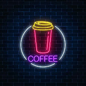Neon glowing sign of coffee cup in circle frame on a dark brick wall background. Fastfood light billboard sign.