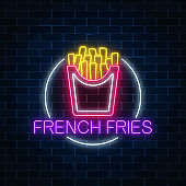 Neon glowing sign of burger in circle frame on a dark brick wall background. Fastfood light billboard symbol.
