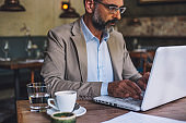 Businessman using laptop at cafe