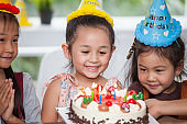 group of happy children girl with hat blowing candles on  birthday cake together celebrating in party . adorable kids gathered around birthday cake multiethnic