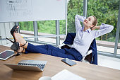 business woman relaxing or sleeping with her feet on the desk in office. female boss worker close eyes sitting with legs on the table in the resting time at work place