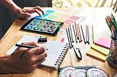 Fashion Designer Stylish Concept, Young dressmaker or designer drawing design sketch working for clothes and Choose color bar in digital tablet in manufacturing office studio
