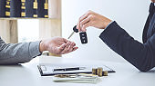 Salesman send key to customer after good deal agreement, successful car loan contract buying or selling new vehicle