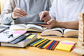 Education, teaching, learning concept. High school students or classmates group tutor in library studying and reading with helps friend doing homework and lesson practice preparing exam to entrance