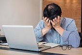 Image of Frustrated stressed business man and graph business with computer laptop in the workplace