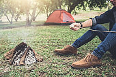 Young Man hiking cooking a marshmallow candies on the campfire in forest, hike and people concept - happy relaxation camping