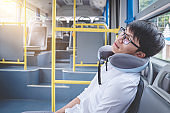 Young Asian man traveler sitting on a bus and sleeping with pillow, transport, tourism and road trip concept