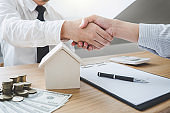 Real estate broker agent and customer shaking hands after signing contract documents for ownership realty purchase, Concept mortgage loan approval