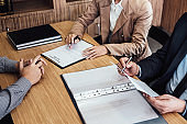 Two senior manager reading a resume during a job interview, Employer interviewing to ask young male job seeker for recruitment talking in office