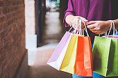 Fashion shopping girl, Young woman carrying colorful shopping bags while walking along the shopping mall