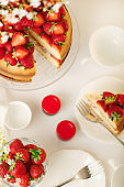 Homemade strawberry cake on a glass stand on the white background.