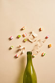 Champagne bottle with colorful party items on light yellow background. Flat lay.