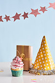 Birthday party background with cupcake, party hat and present