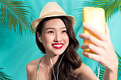 Fashion pretty woman with hat standing and taking selfie photo over colorful blue background