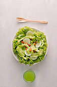 Fresh salad with tomatoes, cucumbers and lettuce on a wooden background