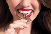 Closeup of a woman with red lipstick eats chocolate