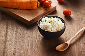 Grains of rice in a wooden bowl and ingredients for a vegetarian recipe - healthy eating concept