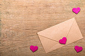 Small pink hearts and envelope on wooden background. Copy space. Valentine's day background.