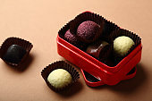 Truffle chocolate candies in red gift box, food closeup
