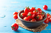 Cherry tomatoes in ceramic bowl on blue rustic wooden background.