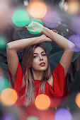 Beautiful young woman in red dress and colorful bokeh effect