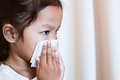 Sick asian little child girl wiping and cleaning nose with tissue on her hand in the hospital