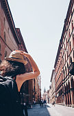 Girl with hat looking up old house in Bologna - The city of the culture - Travel in Italy