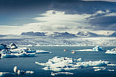Landscape view of Jokullsarlon lagoon with floating ice and boats, Iceland