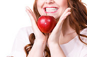 Woman holds apple fruit close to face, isolated