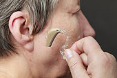 Closeup senior woman using hearing aid