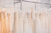 Rack with many wedding dresses.
